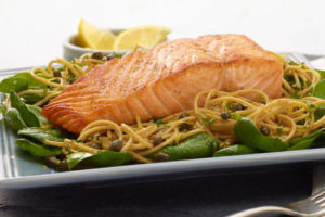 Salmon with basil in a pasta dish.