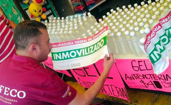 A Profeco agent seizes a product being sold as hand sanitizer.